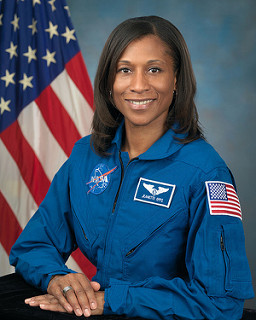 Portrait picture of Jeanette Epps in blue astronaut jumpsuit with hands folded and an American flag in the background