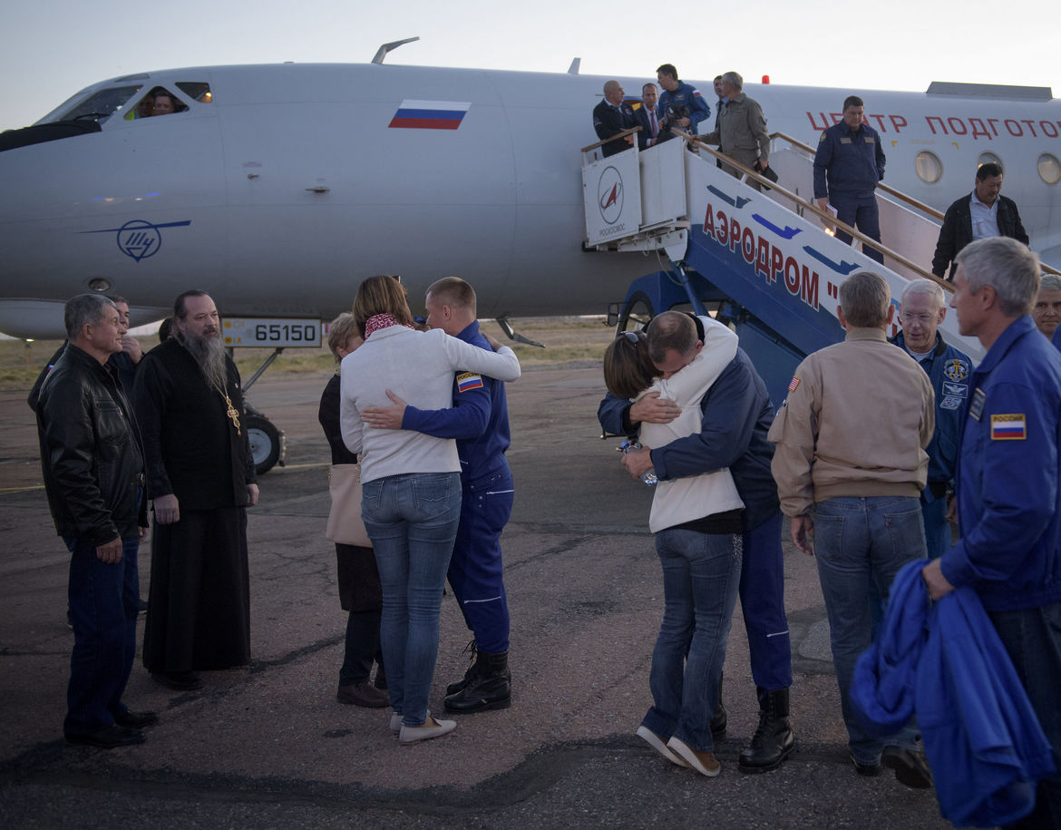Cosmonaut  Alexey Ovchinin (left) and astronaut Rick Hague (right) embrace their families after returning to Kazakhstan. Their flight to the ISS failed to achieve orbit after a Russian Soyuz rocket failed during launch. Credit: NASA/Bill Ingalls