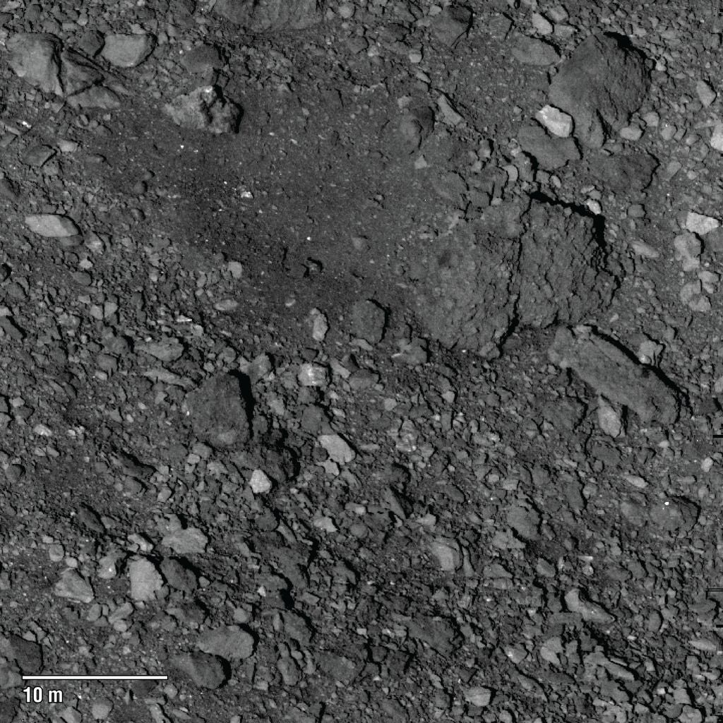 A relatively rare clear(ish) spot (top center) on the surface of Bennu is a candidate for the OSIRIS-REx spacecraft to land and collect a sample of the asteroid. This was taken from a distance of about 5 km. Credit: NASA/Goddard/University of Arizona