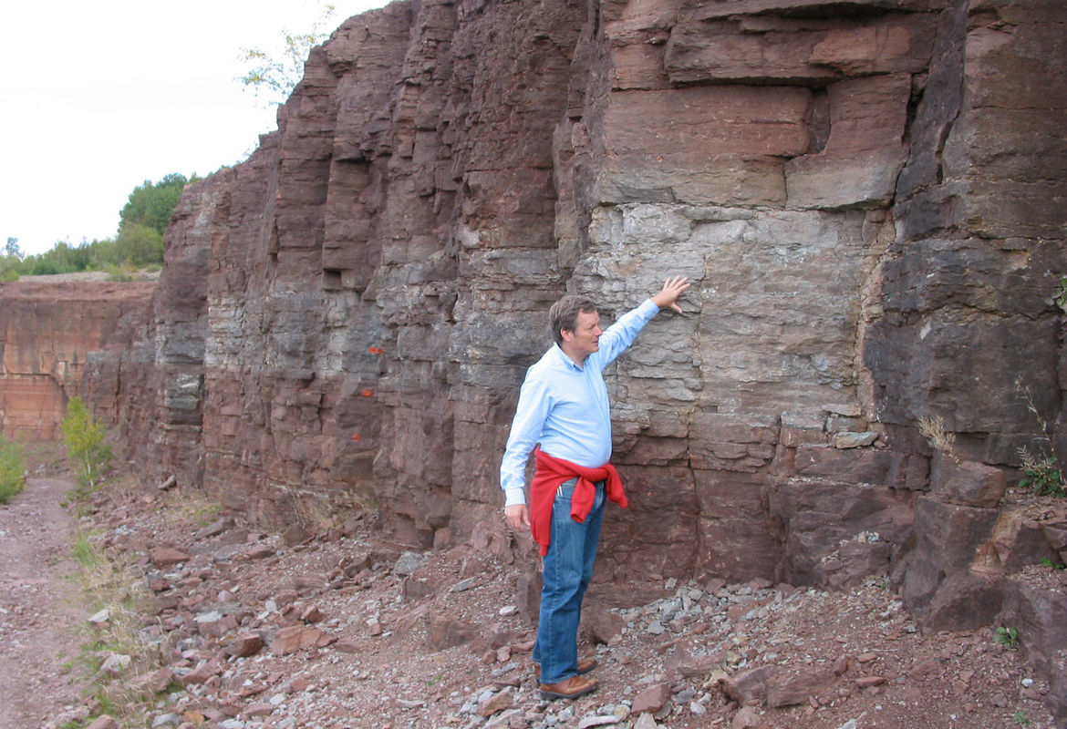 Lead author of the study Birger Schmitz stands in front of the Ordovician sediment layer at a quarry in Kinnekulle, Sweden, one site they examined for evidence of dust from a giant asteroid collision 466 million years ago. Credit: Philip R. Heck