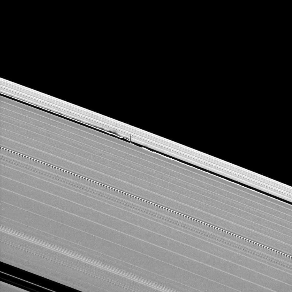 The tiny moon Daphnis creates vertical waves in Saturn's rings.