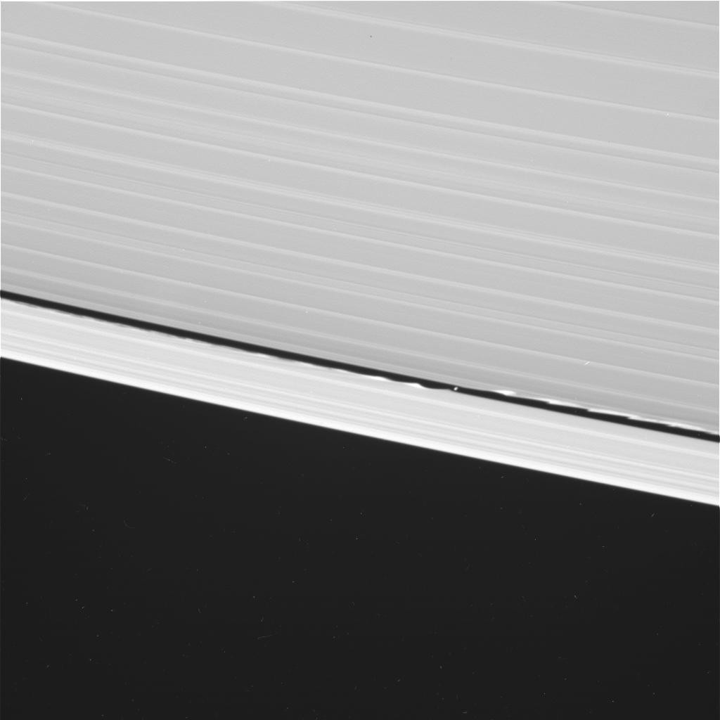 Cassini took this wide-angle shot of Daphnis around the same time as the narrow angle one. Note how far the waves go around the rings. Saturn is to the upper right. This is a raw image, so there are some blemishes that aren't real objects. Credit: NASA/JP