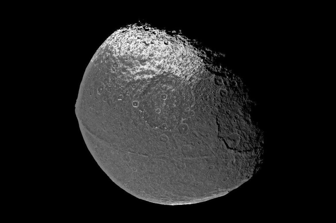 Iapetus is a moon of Saturn, and has a very weird ridge of mountains going all the way around its equator. Credit: Cassini Imaging Team, SSI, JPL, ESA, NASA