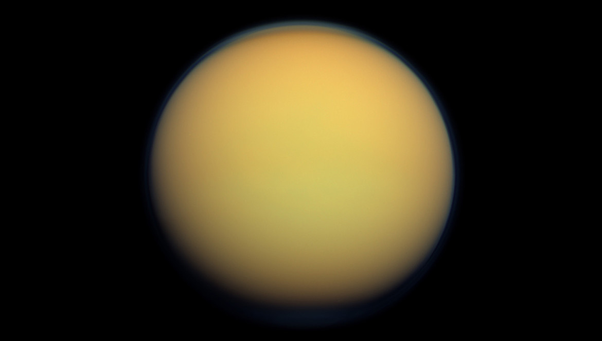 Cassini image of Titan; you can see the haze layer over the north pole. The moon is shrouded in thick haze, giving it that yellowish appearance and hiding surface features. Credit: NASA/JPL-Caltech/SSI