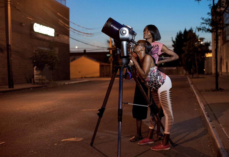 Two women observe Saturn through a telescope.