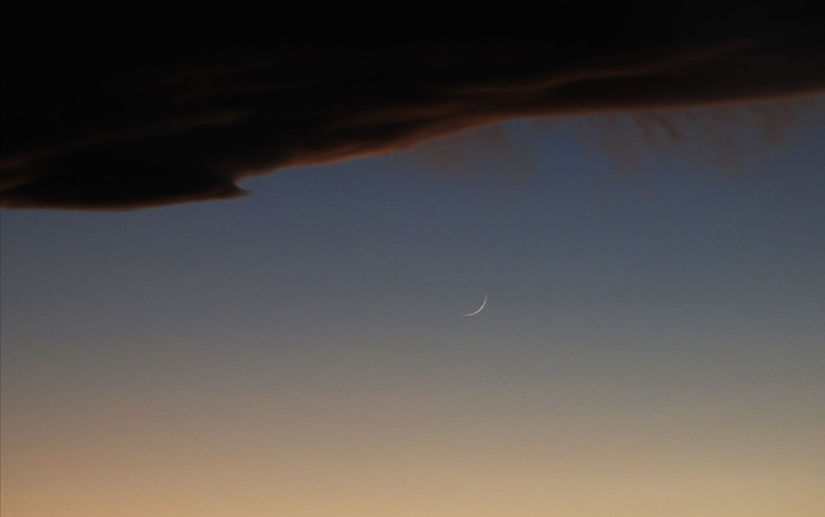 The thin crescent Moon sets just under the cloud bank caused by air rising dramatically over the Rocky Mounatins. Credit: Phil Plait