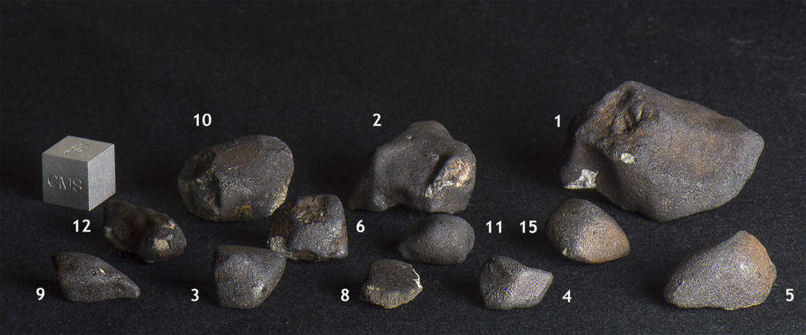 A dozen of the Dishchii'bikoh meteorites collected in Arizona. The cube on the left is for scale, and is one centimeter on a side (the size of a normal six-sided die). Credit: Jenniskens et al.