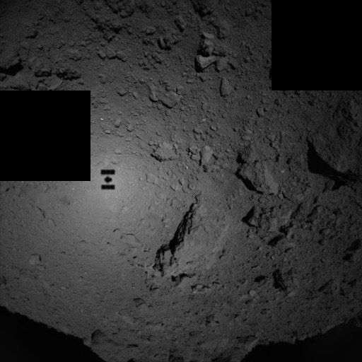 This view of the asteroid Ryugu was taken when Hayabusa-2 was only 80 meters above the surface! The shadow of the spacecraft can be seen too. Credit: JAXA