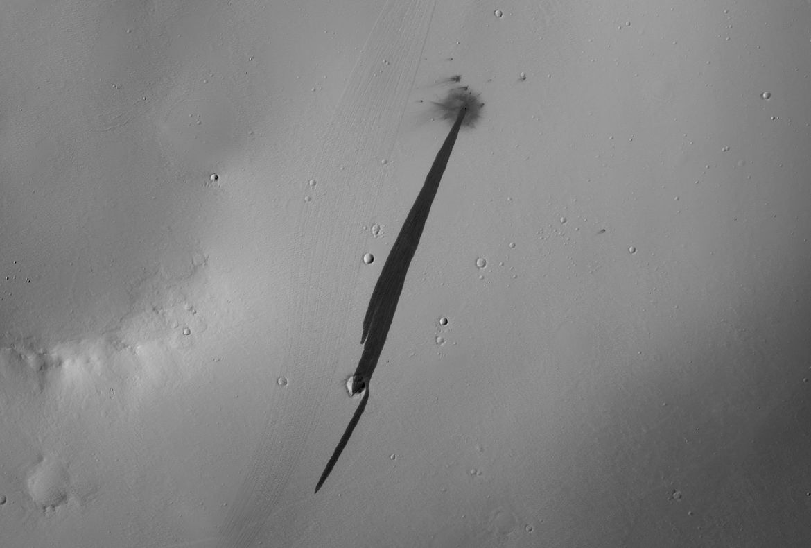 A tiny asteroid impacted Mars, releasing an avalanche of dust that left behind a dark streak on the surface. Credit: NASA/JPL/University of Arizona