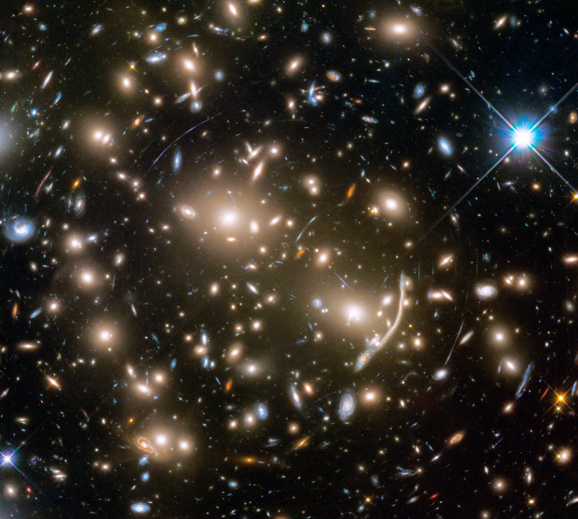 Abell 370 is a galaxy cluster about 4 billion light years from Earth. Its gravity causes light from galaxies behind it to bend, called gravitational lensing. Credit: NASA, ESA, and J. Lotz and the HFF Team (STScI)