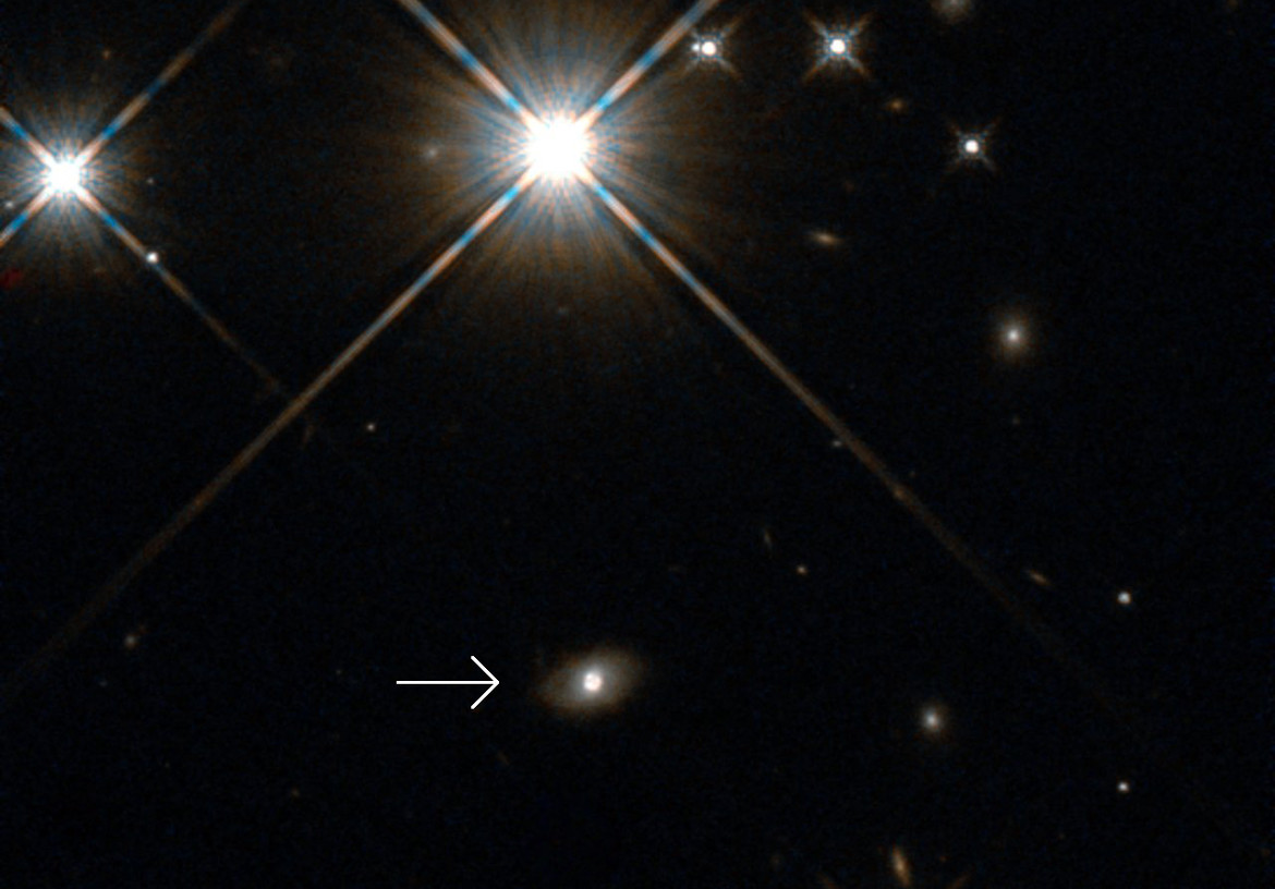 Hubble's view of the galaxy that acted as the lens for the supernova (indicated by arrow). It's actually a rather faint galaxy, and the lensed explosion is the bright blob in the middle. Credit: ESA/Hubble, NASA