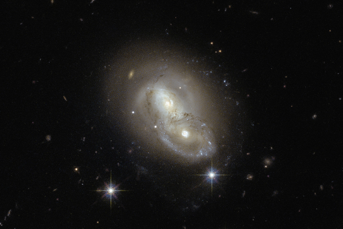 A closer look at IRAS 06076-2139. The southern galaxy (lower right) has suffered at least one collision in the past; note the ring structure around the core, evidence a smaller galaxy plowed through it. Credit: ESA/Hubble & NASA