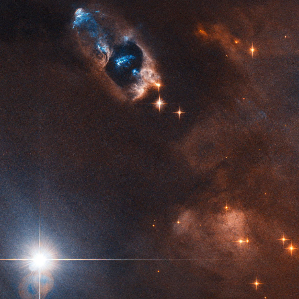Young stars in the nebula NGC 1333 blast out twin beams of matter, creating eerie blue glows in this Hubble image. Credit: ESA/Hubble & NASA, K. Stapelfeldt; CC BY 4.0