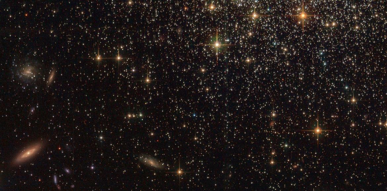 Background galaxies litter the sky far, far behind the globular cluster NGC 1466. Credit: ESA/Hubble & NASA