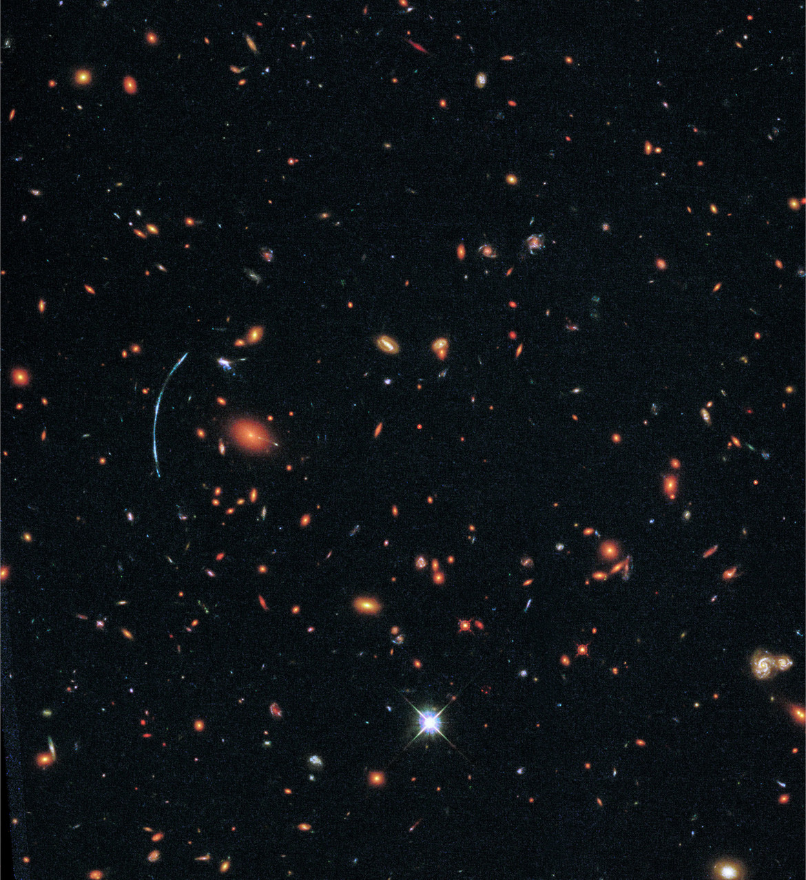 The galaxy cluster SDSS J1110+6459 can be seen here in the as hundreds of galaxies held together by their mutual gravity. The blue arc of the lensed galaxy SGAS J111020.0+645950.8 can be seen on the left.