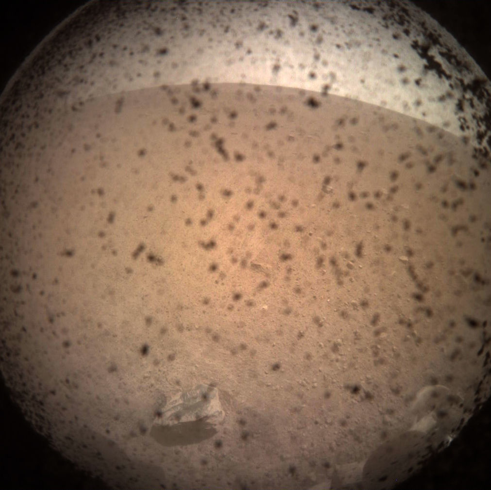 The very first image from NASA's Mars InSight lander sitting on the surface of Mars. Dust particles on the dust cover obscure things somewhat, but the surface of Mars and the curved horizon (due to the wide-angle lens) are obvious, including a rock nearby