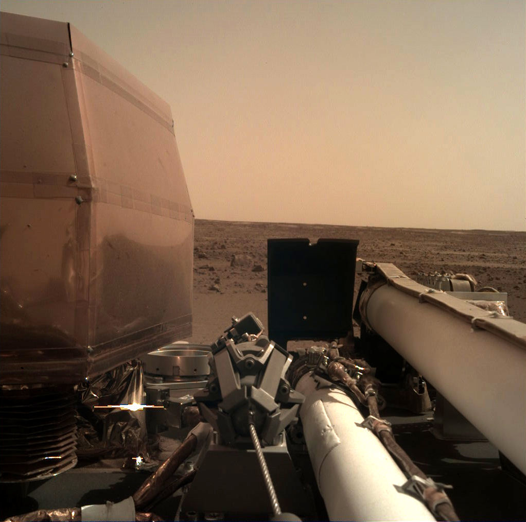 First light for the Instrument Deployment Camera on NASA's Mars InSight lander. You can see various instruments on the deck, including the segments of the robot arm, and Mars beyond. Credit: NASA/JPL-Caltech