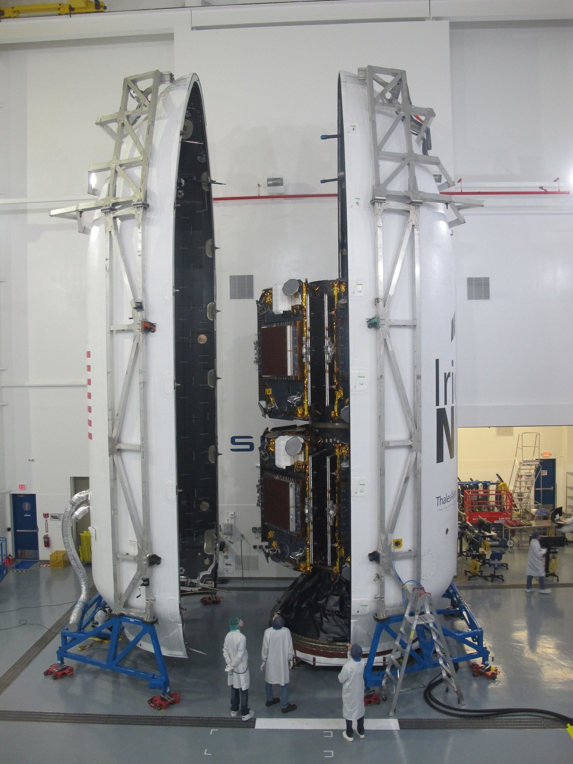 Ten Iridium NEXT satellites are mounted inside the SpaceX Falcon 9 payload fairing, ready to be places on top of the rocket stack. Note the people at the bottom for scale. Credit: Iridium