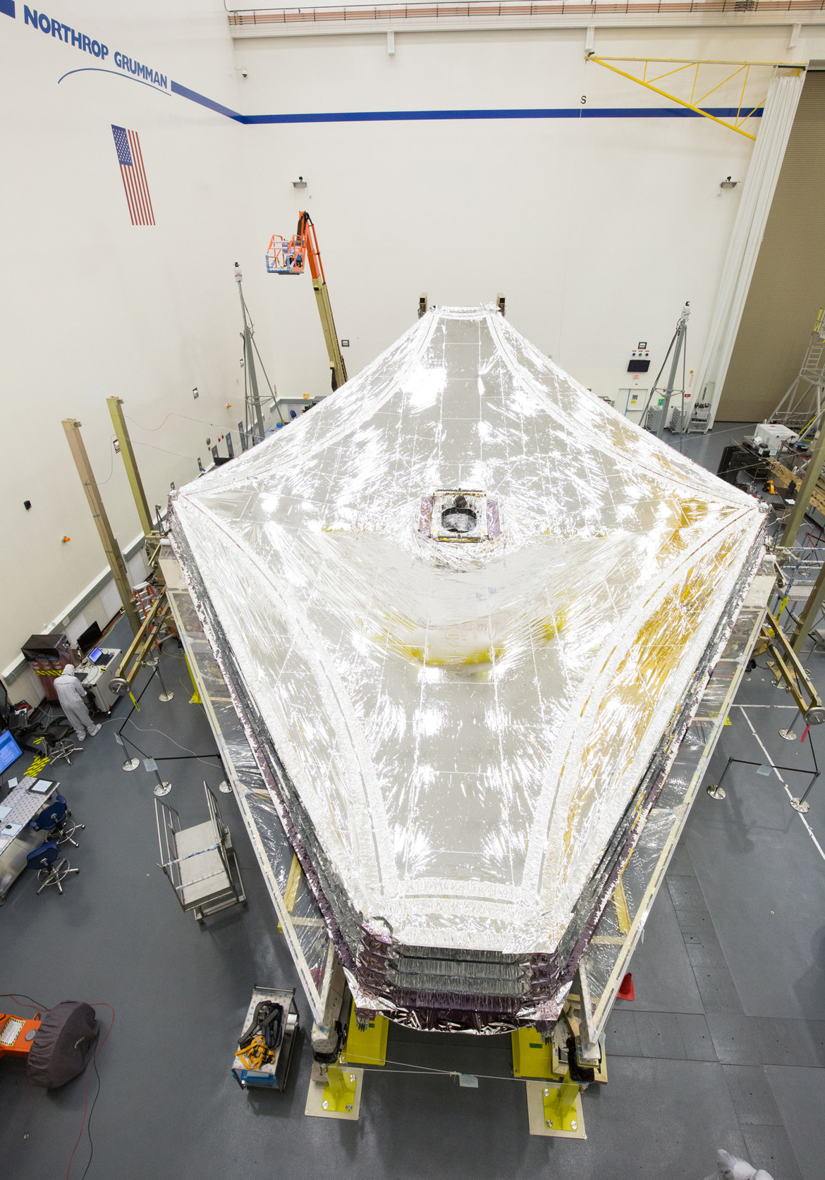 The fully-deployed and under-tension sunshield for JWST in a clean room in California. Credit: Northrup Grumman