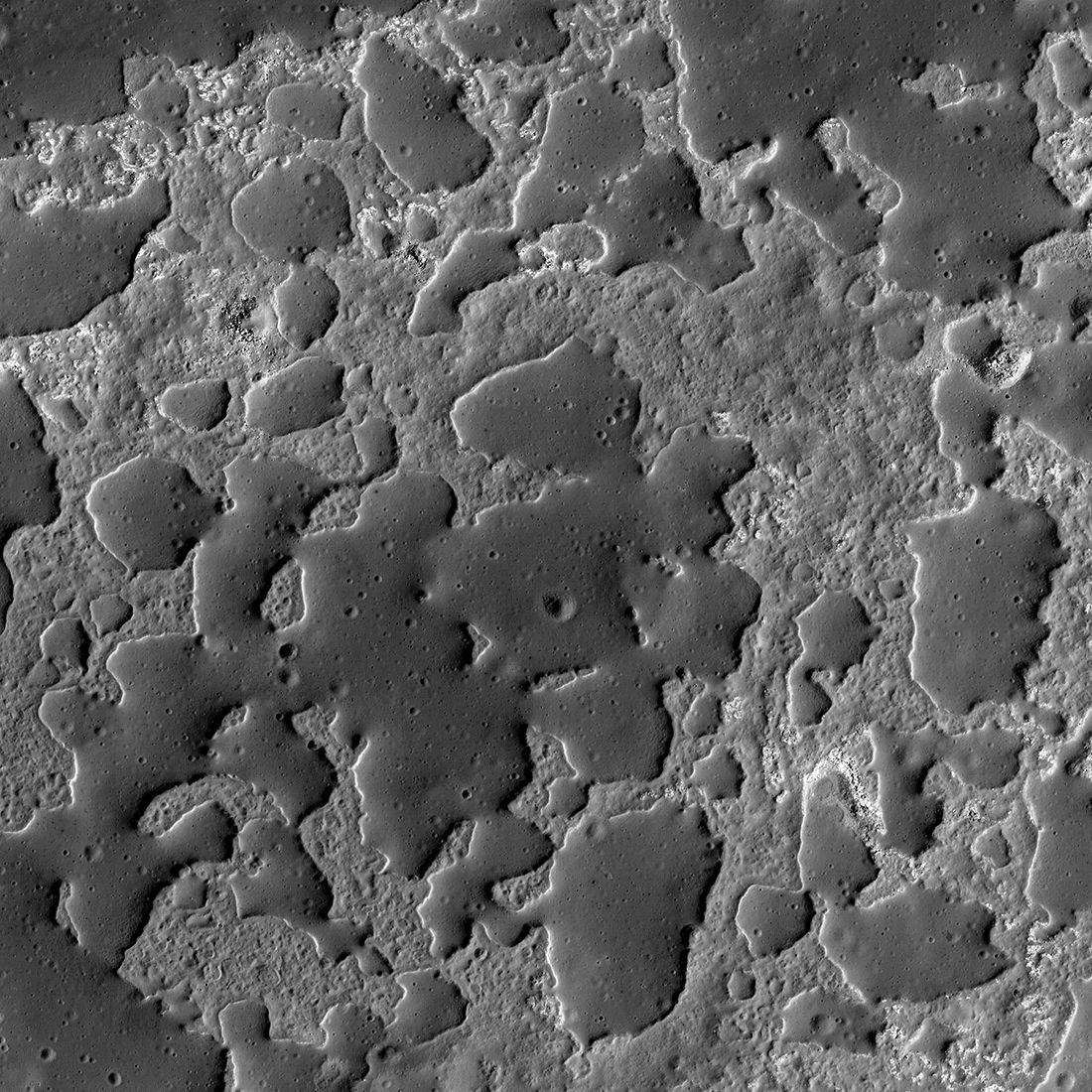 Zooming in on the strange structures in Ina, the smooth regions are cratered and elevated about a rougher, lower terrain. Credit: NASA/GSFC/Arizona State University