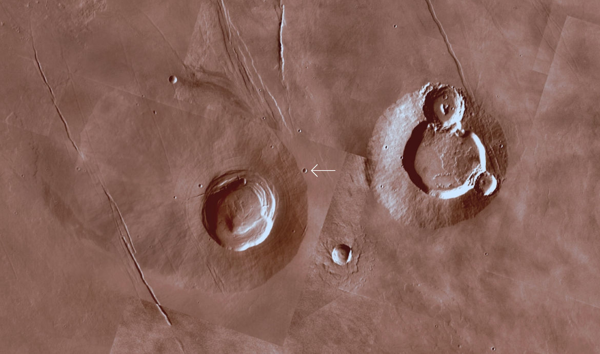 The area around a Martian crater for context shows two large volcanoes nearby (the famous and much larger Tharsis volcanoes are off to the lower right). The image is about 420 km across. Credit: Mars Trek/NASA/JPL-Caltech