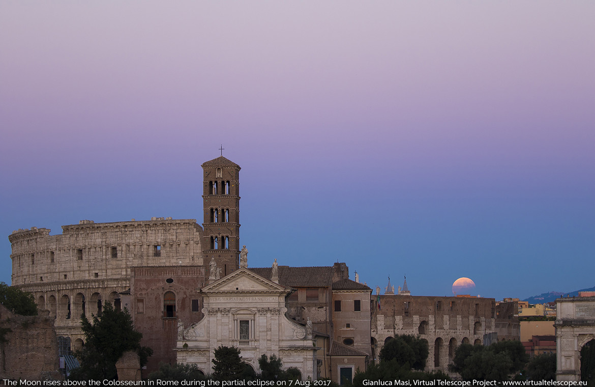 The partially eclipsed Moon rises over the Roman Colosseum.