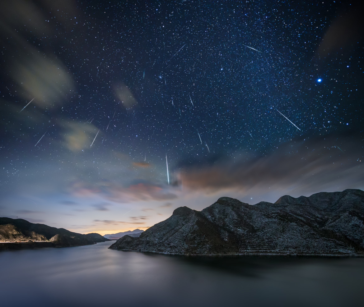 Several Geminids meteors falling over a lake and mountain range in China