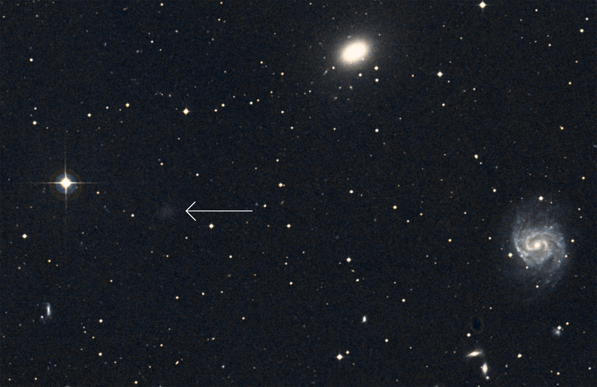 NGC 1052-DF2 (arrowed) can barely be seen in earlier images (like in this one from the Digitized Sky Survey), and it's easy to overlook. Credit: Simbad / Aladin