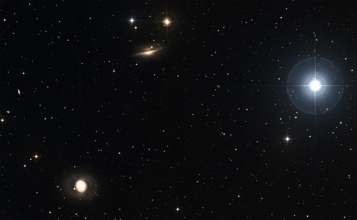 The area of the sky around NGC 1055 (center top) shows the bright star Delta Ceti (right) and another galaxy, M 77 (lower left). The two galaxies may have interacted in the past. Credit: SIMBAD / Aladin / DSS