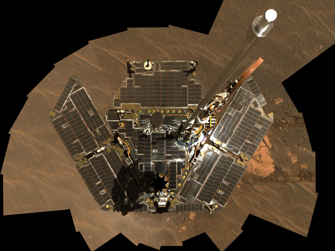 A self-portrait of Opportunity taken by combining several images. The camera is located on a mast (blocked by the series of black cutouts near the bottom of the image) and cannot be seen when the images are combined.