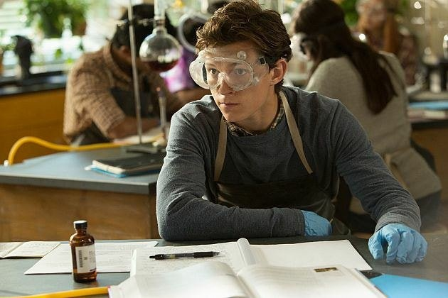 Peter Parker in lab goggles, an apron, and gloves at a science table