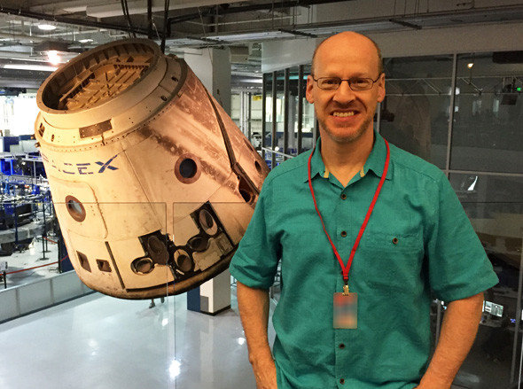 Phil Plait in front of the very first Dragon capsule that went to space. Note the scorch marks. Credit: Phil Plait / SpaceX