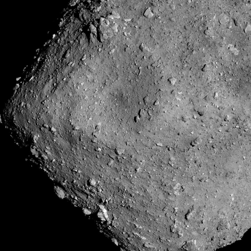 The asteroid Ryugu seen by the spacecraft Hayabusa 2 from a mere 6 kilometers away. The surface is strewn with rubble; objects just over a meter across are visible.