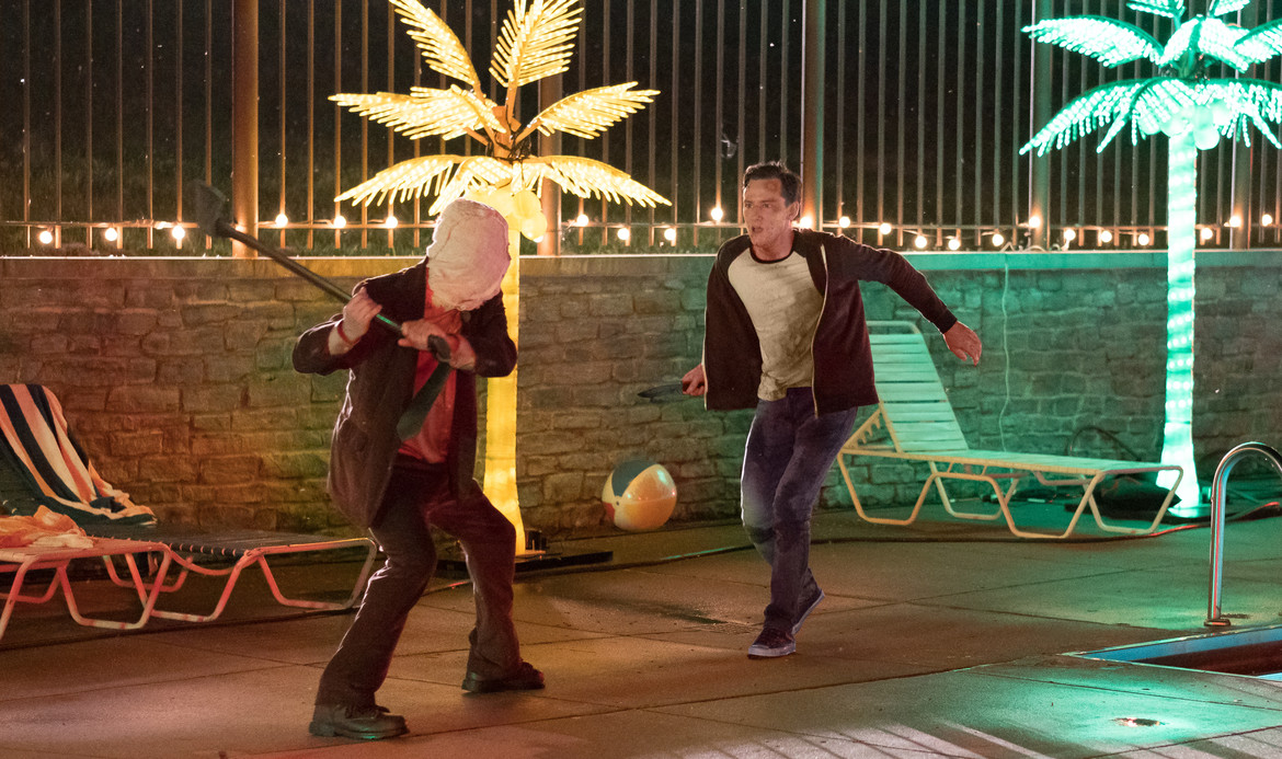 """After being preyed upon by masked villains, Luke (Lewis Pullman) fights back against """"Man in the Mask"""" (Damian Maffei) in THE STRANGERS: PREY AT NIGHT."""