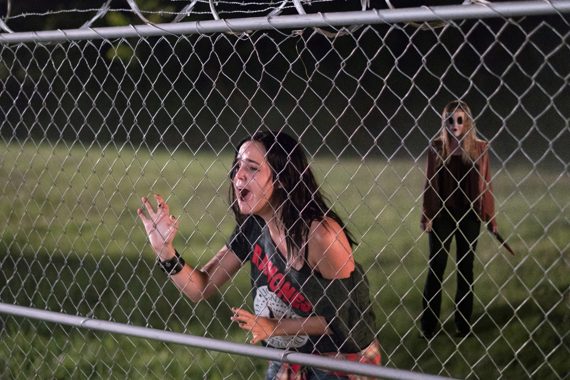 """Kinsey (Bailee Madison) desperately tries to escape from """"Dollface"""" (Emma Bellomy) in THE STRANGERS: PREY AT NIGHT."""