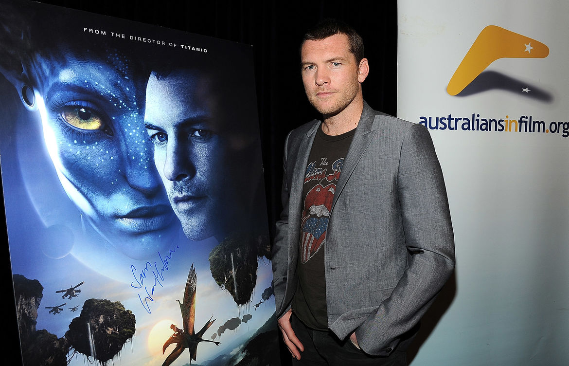 Lead actor Sam Worthington standing in front of a poster for the movie Avatar