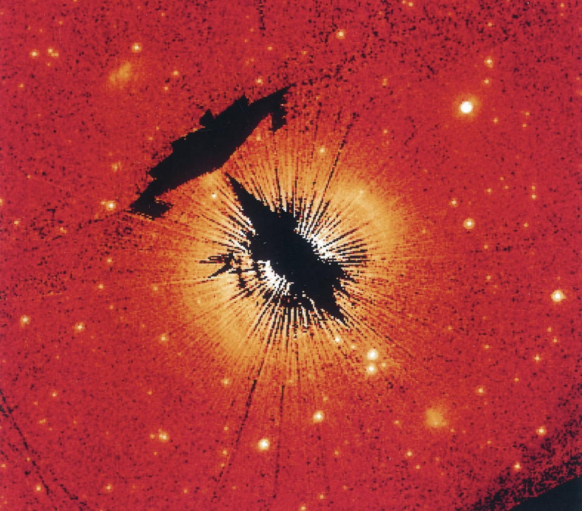 STIS image of HD 163296 with the star blocked behind a metal bar, showing the faint disk of gas and dust around it. The blacked out sections are processing artifacts made when removing the bar in multiple (rotated) images). Credit: Grady et al.