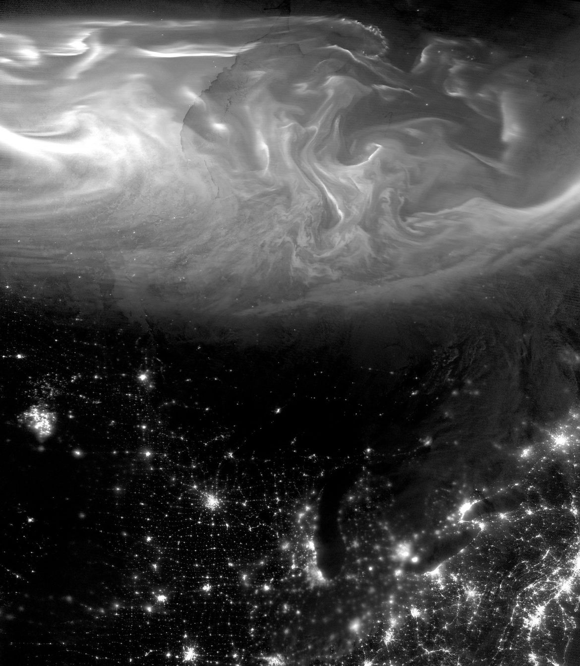 The aurora swirls in northern Canada while the lights from US cities illuminate the night… as well as something else ominously glowing in the American Upper Midwest.