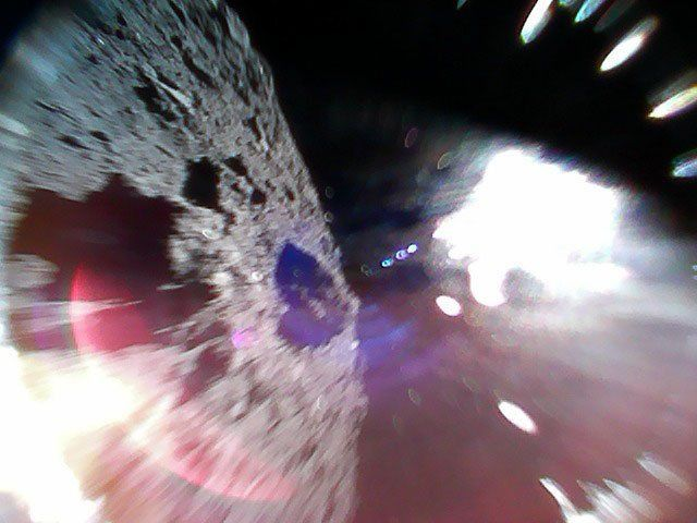 An image caught mid-bounce of the MINERVAII-1 A rover showing the surface of the asteroid Ryugu (left) and a reflection of sunlight (right).  Credit: JAXA