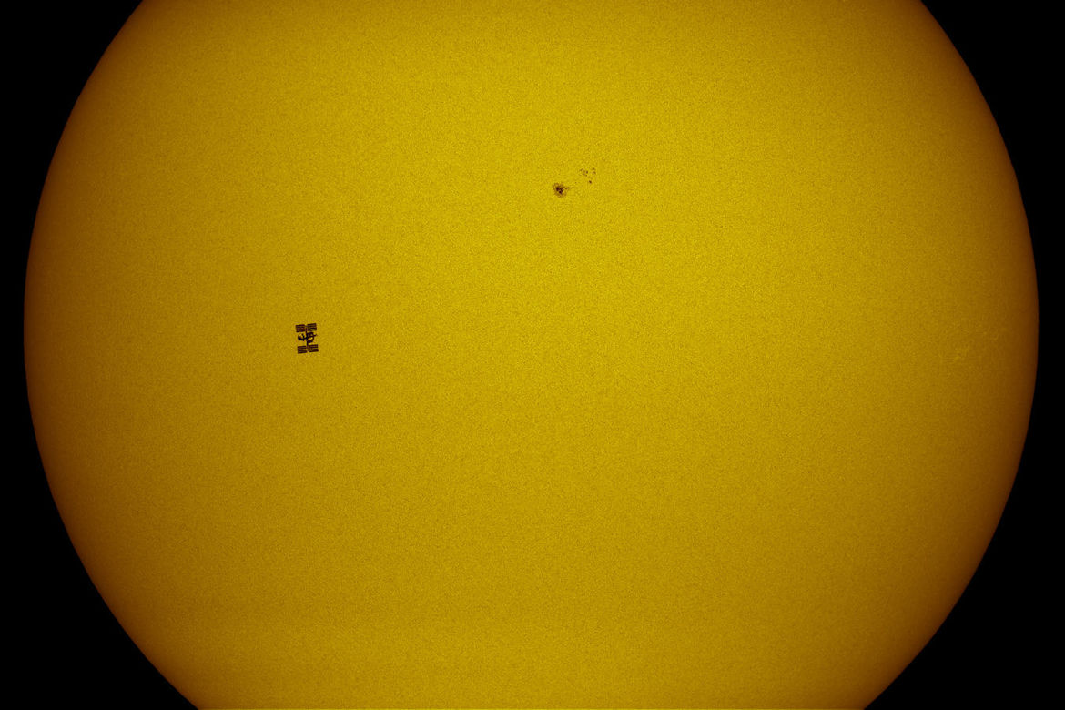 The space station transiting the Sun. The sunspot to the upper right is about the same size as the Earth ... but a lot farther away than ISS. Credit: Thierry Legault
