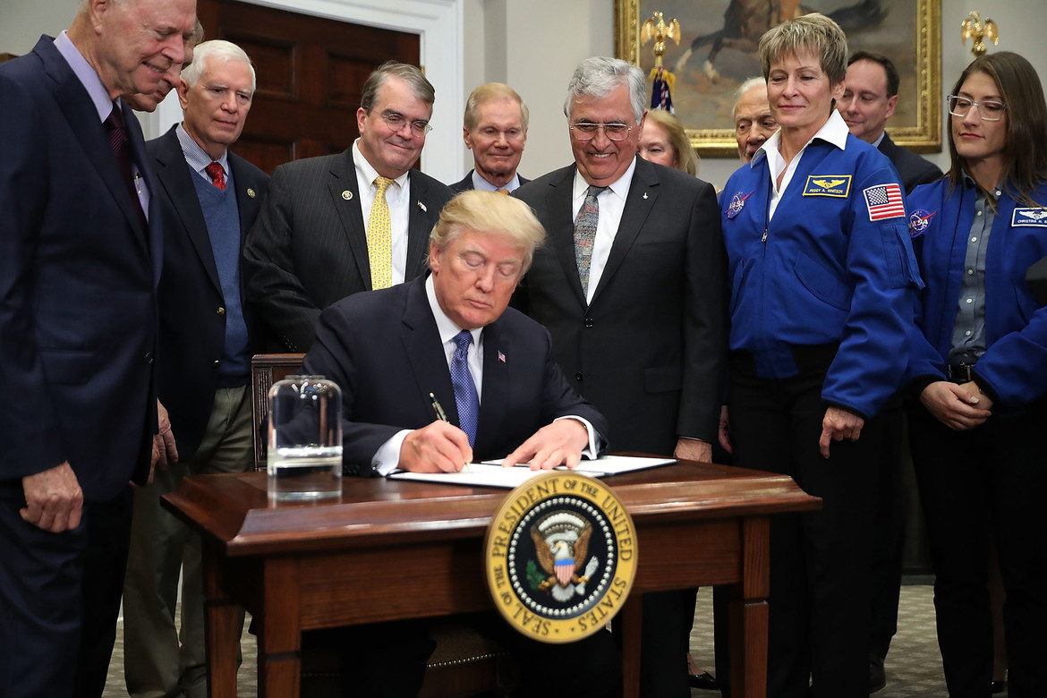 On December 11, 2017, President Trump signed the National Space Policy directive.  Astronaut Harrison Schmitt presented him with an Apollo figurine as astronaut Peggy Whitson (right) looks on. Credit: Chip Somodevilla/Getty Images