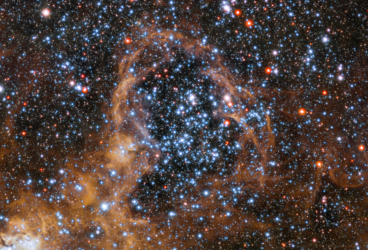 Detail of the Tarantula Nebula of a cluster of stars plowing up gas around them into a thin shell. Credit: ESO