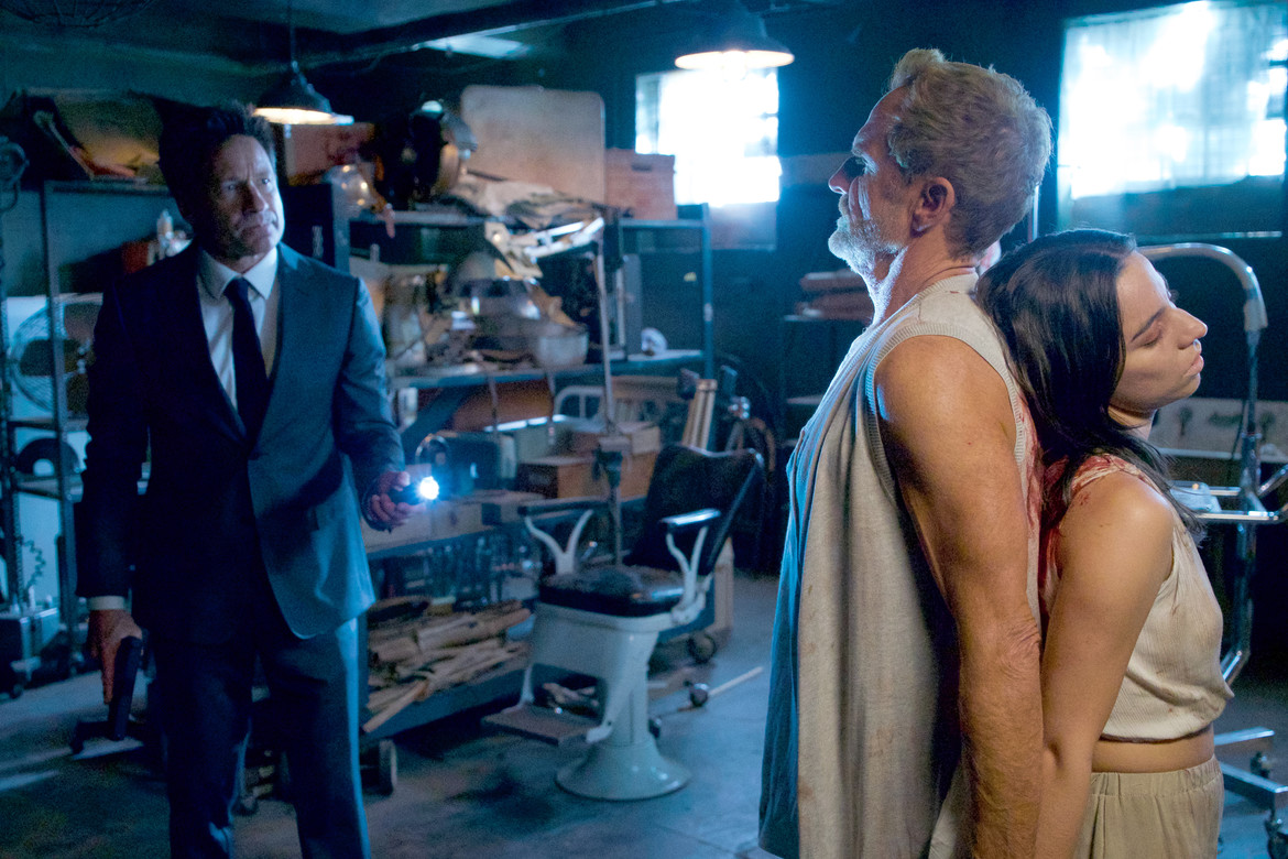 The X-Files episode 1109 Nothing Lasts Forever - Mulder with cult members attached at the back