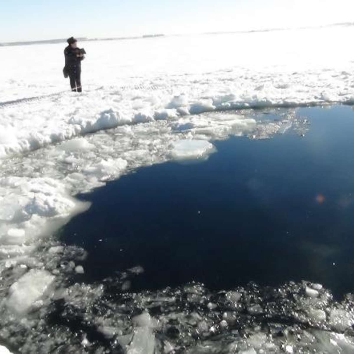 A hole in the frozen surface Lake Chebarkul made by the impact of a half-ton chunk of the Chelyabinsk meteorite on Feb. 15, 2013. We now have video of this event. Credit: ITAR-TASS Itar-Tass Photos/Newscom