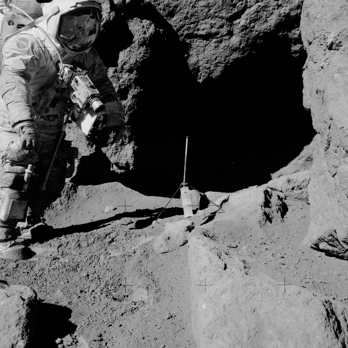 Gene Cernan, from Apollo 17, stands next to a gnomon used to measure slope and rock characteristics. On the Moon. Credit: NASA