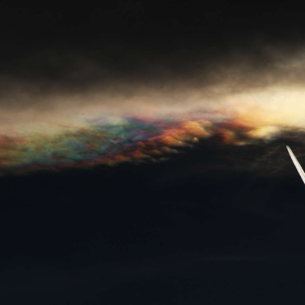 Contrast-enhanced view of iridescent lenticular clouds over Boulder, Colorado. Note the airplane. Credit: Phil Plait