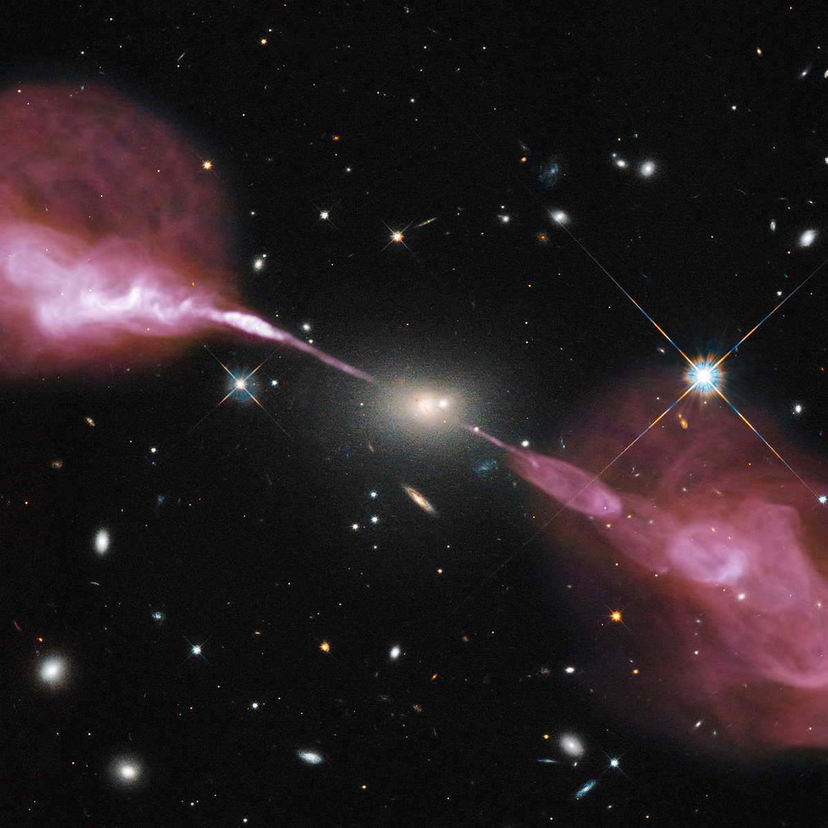 Hercules A is a relatively nearby active galaxy, with a black hole in its heart eating matter and blasting out huge amounts of radiation and matter.