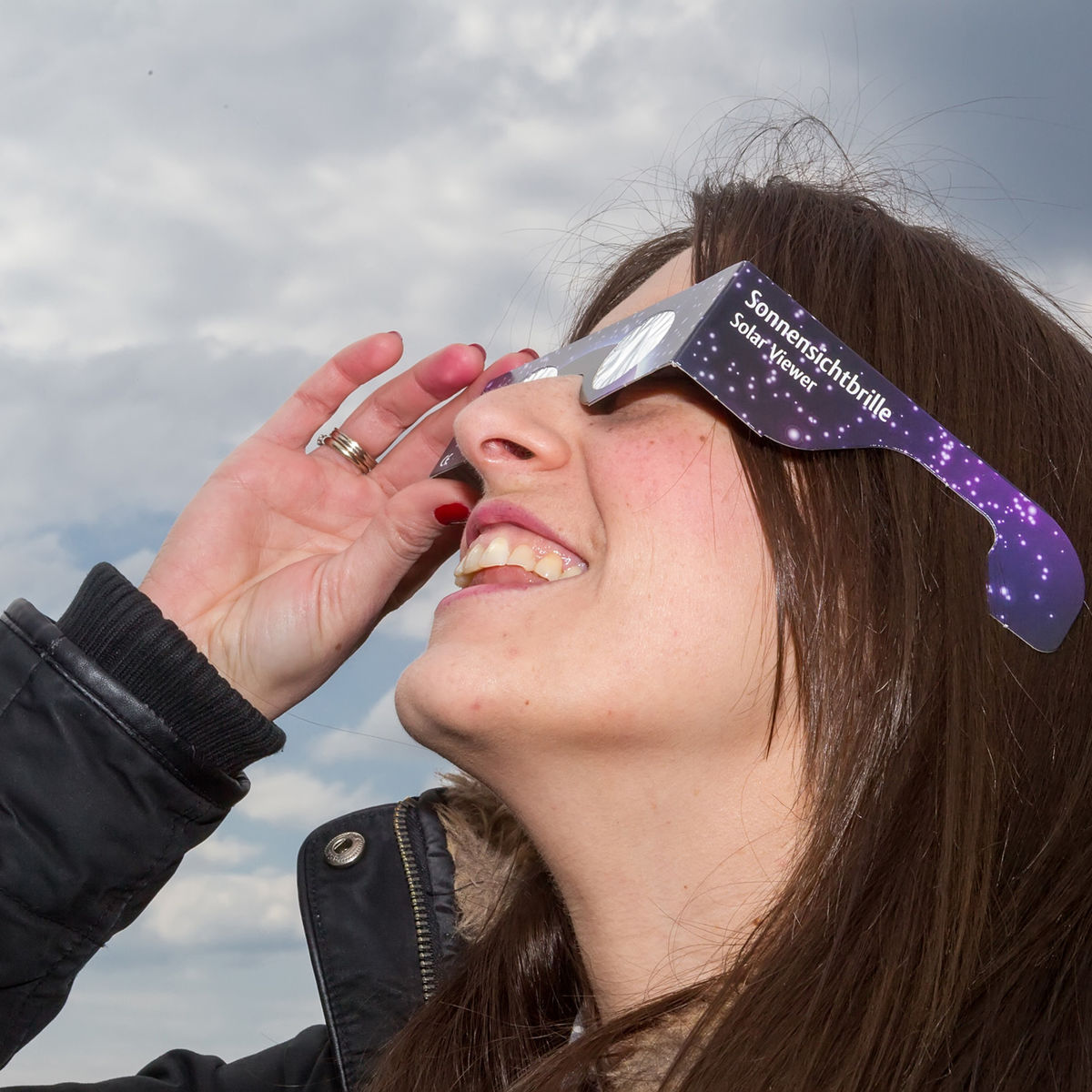 a woman uses safe glasses to view an eclipse