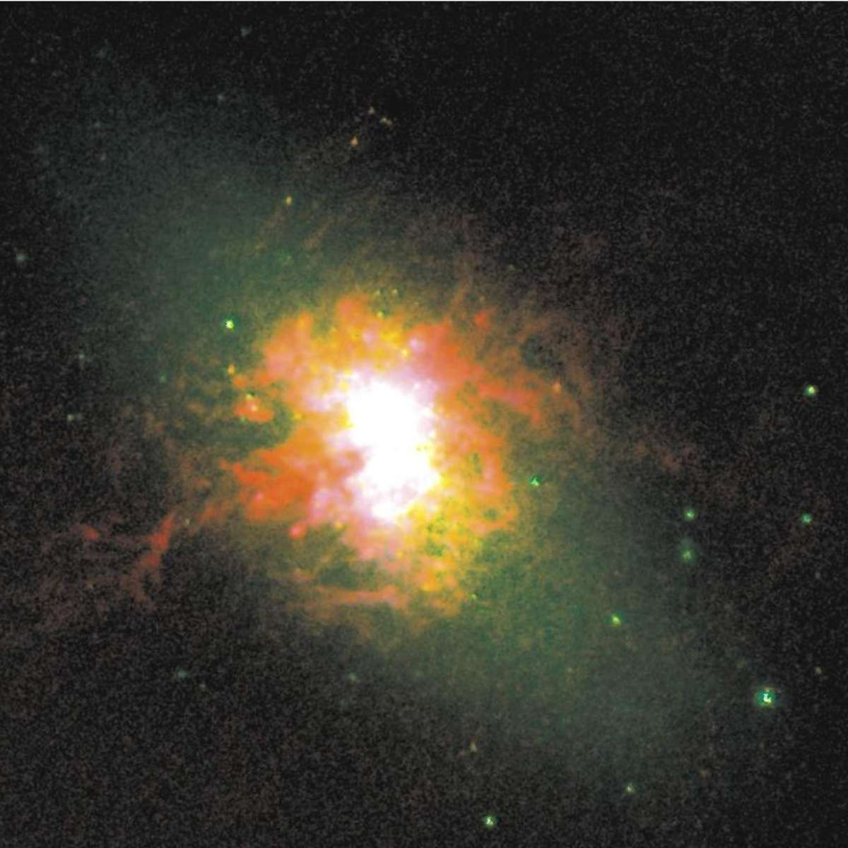 NGC 5253, a starburst dwarf galaxy. Starlight is shown in green, yellow is warm gas, and red is gas being blasted by all the young hot stars in the galaxy. Credit: Jordan Zastrow