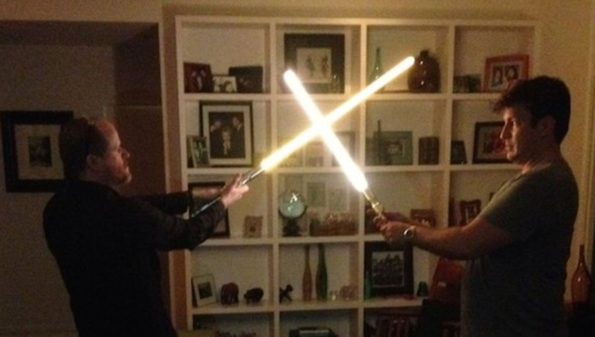 photo-of-joss-whedon-and-nathan-fillion-locked-in-lightsaber-duel-1.jpg